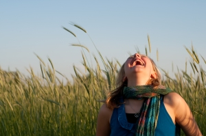 girl laughing in a wheat field under a clear sky. This file is licensed under the Creative Commons Attribution-Share Alike 2.0 Generic license.